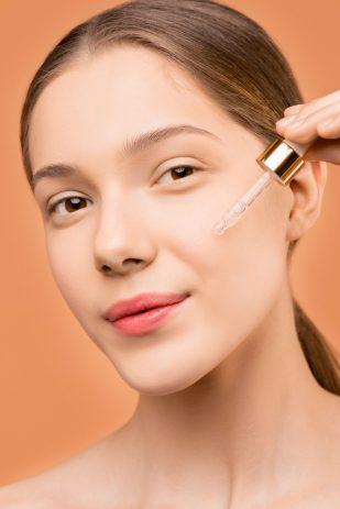 Mujer echándose aceite en la cara