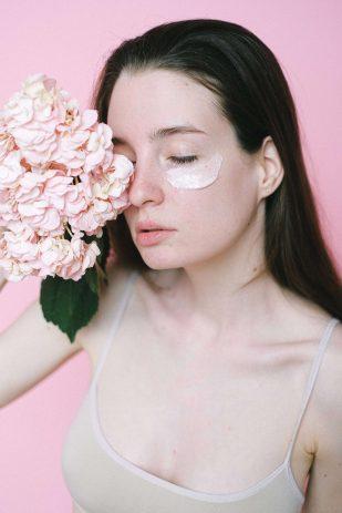 Chica con rosas y crema en la cara